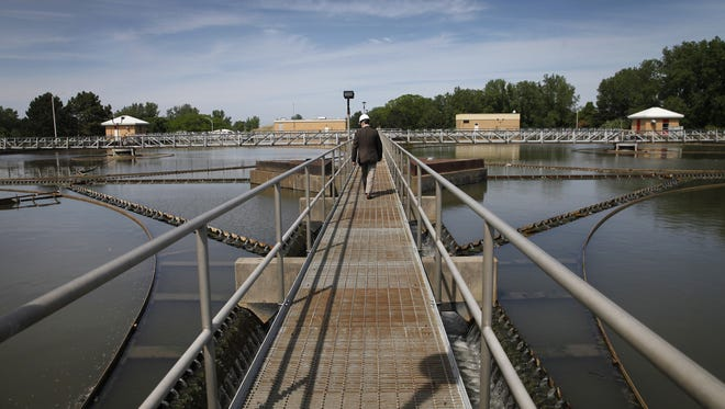 Michael J. Garland, director of environmental services for Monroe County, walks a ramp between skimmers at the Frank E. VanLare Wastewater Treatment Facility. Skimmers allow solid waste to settle to the bottom and surface skimmers on top collect surface scum.
