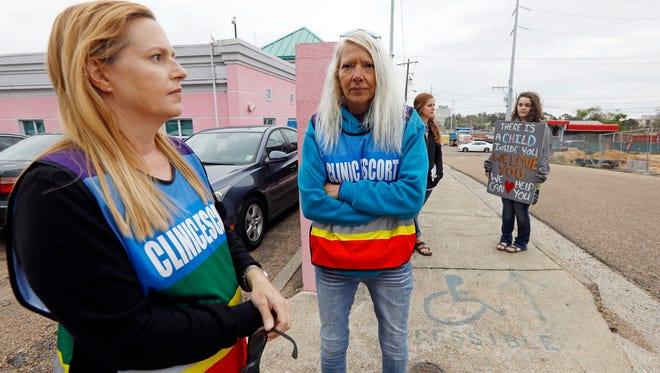 Clinic escorts Kim Gibson, left, and Derenda Hancock, second from left, and anti-abortion sidewalk counselors Beka Tate, second from right, and a woman who only gave her first name, Lauren, stand outside the Jackson Women's Health Organization's clinic, the only facility in the state that performs abortions, on  March 20, 2018 in Jackson, Miss. A federal judge temporarily blocked a new Mississippi law that bans abortion after 15 weeks, the most restrictive abortion law in the United States.