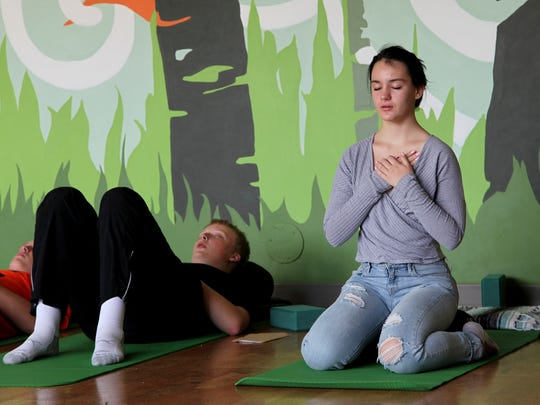 Nora Pearson, (right), practices mindful breathing during the Mindful Studies class at Wilson High School in Portland, Ore. The year-long course is one of a growing number of programs that are incorporating mindfulness, yoga and meditation into school curriculums to bring socio-emotional benefits to students.