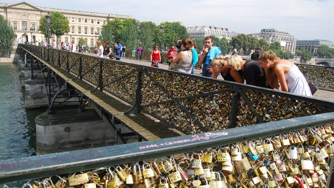 Visitors check out the padlocks left by lovers on Paris' Pont des Arts pedestrian bridge.  The mass of the padlocks is threatening the bridge and boats below.