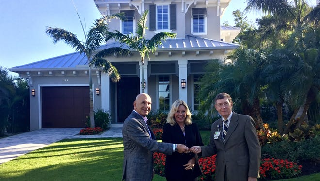 Naples residents Sam and Cindy Scalise stand outside a home they donated to the NCH Healthcare System. Pictured with the couple is Dr. Allen Weiss, the president and CEO of the hospital system.