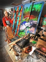Doug Arnholter shows off samples of his paint-by-numbers community works.