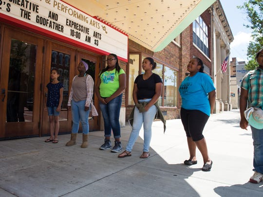 """Singers warm up their vocal cords outside the Bohm Theatre for the upcoming production of """"History Repeats Itself."""""""