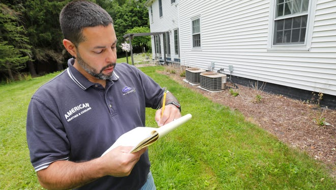 Anthony Ortiz with American Heating and Cooling of Poughkeepsie surveys a home in Poughkeepsie to determine where to drill for a geothermal heating and cooling system for the home on June 15, 2018. The family is migrating energy consumption from traditional sources to solar and geothermal reducing their dependency on external sources.