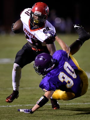 Overton tailback Taveruis Travis (28) powers through Lipbscomb cornerback Connor Christian (30) as he runs the ball during the first half of their game Friday Sept. 11, 2015, in Nashville, Tenn.