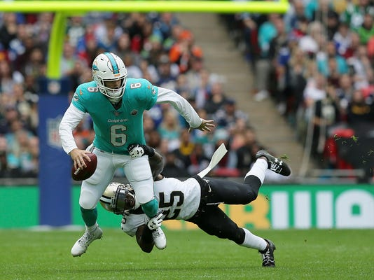 Miami Dolphins quarterback Jay Cutler (6) is tackled by New Orleans Saints defensive back Rafael Bush (25) during the first half of an NFL football game at Wembley Stadium in London, Sunday Oct. 1, 2017. (AP Photo/Tim Ireland)