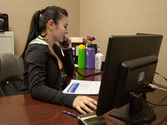 Ahlai Narcisse works at a local insurance agency Friday,