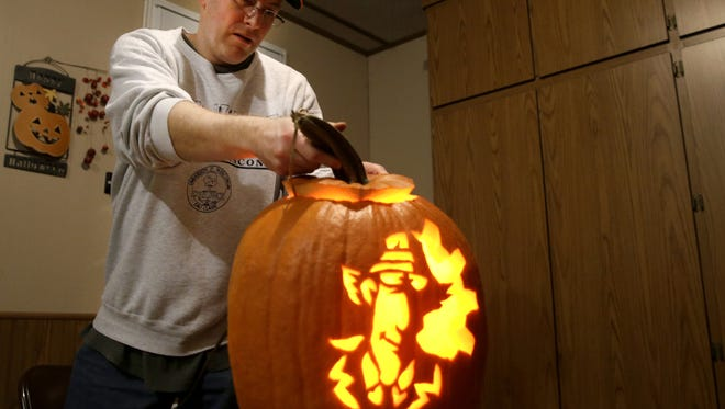 Kevin Rades uses a light bulb to show a finished Inspector Gadget pumpkin that will be part of his annual Halloween display.