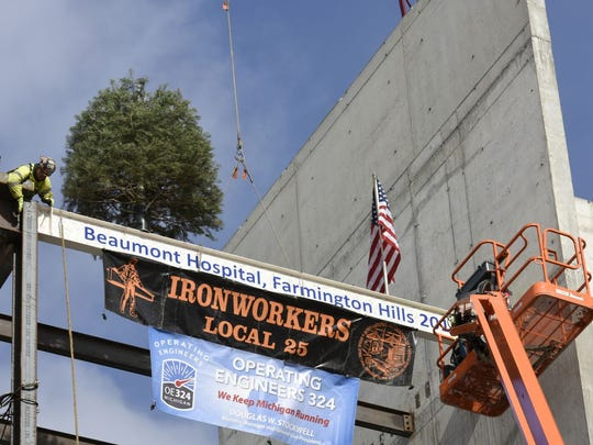 Workers place the traditional tree along with the final beam.