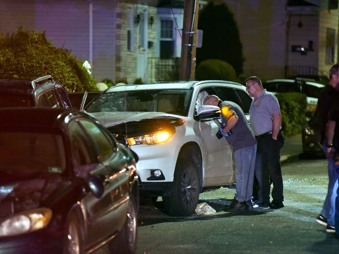 Crime Scene Investigators look inside a car that crashed