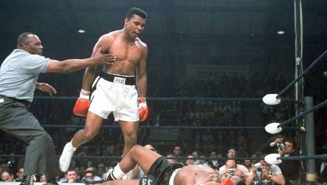 FILE - In this May 25, 1965, file photo, heavyweight champion Muhammad Ali is held back by referee Joe Walcott, left, after Ali knocked out challenger Sonny Liston in the first round of their title fight in Lewiston, Maine. The bout produced one of the strangest finishes in boxing history as well as one of sports' most iconic moments. (AP Photo/File)