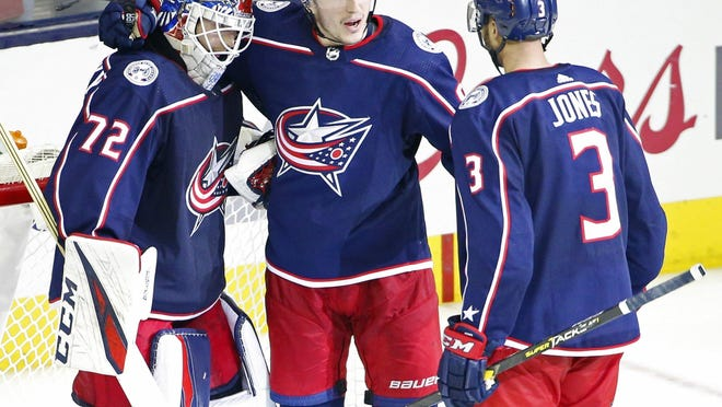 Columbus Blue Jackets defenseman Zach Werenski (8) and Columbus Blue Jackets defenseman Seth Jones (3) hug goaltender Sergei Bobrovsky (72) following the NHL Stanley Cup Playoffs Game 3 against the Tampa Bay Lightning at Nationwide Arena in Columbus on Sunday, April 14, 2019. The Blue Jackets won 3-1.