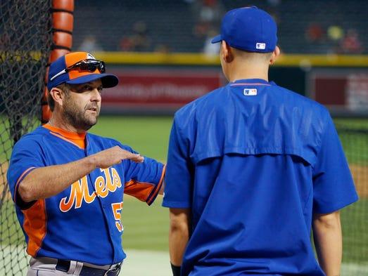 New York Mets hitting coach Kevin Long, left, talks