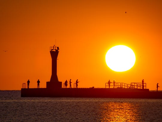 The sun rising on fishermen on Manitowoc's south pier.