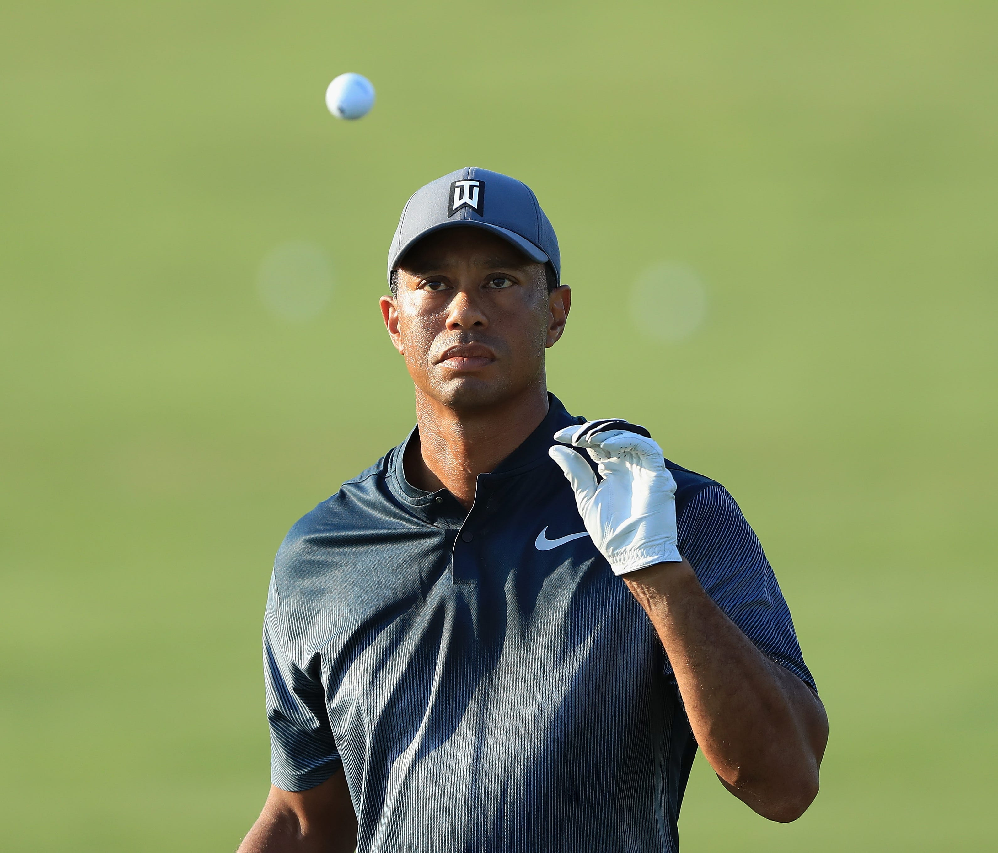 Tiger Woods catches a ball as he warms up on the range prior to playing in the second round of The Players Championship on the Stadium Course at TPC Sawgrass.