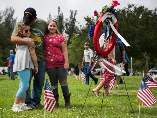 Douglas Milano and his daughters Hannah, 8, left, and Gracie, 10, stop at the memorial wreath following the Memorial Day Service at Coral Ridge Cemetery in Cape Coral on Monday, May 28, 2018.