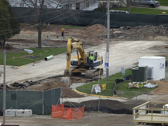 A backhoe digs a trench on a section of former Brookwood Lane at the Titletown District construction site May 4,  2016.