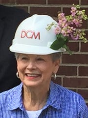 Former Haddonfield Mayor Tish Colombi decorates her hard hat at a groundbreaking ceremony for an archives center for the borough's Historical Society.