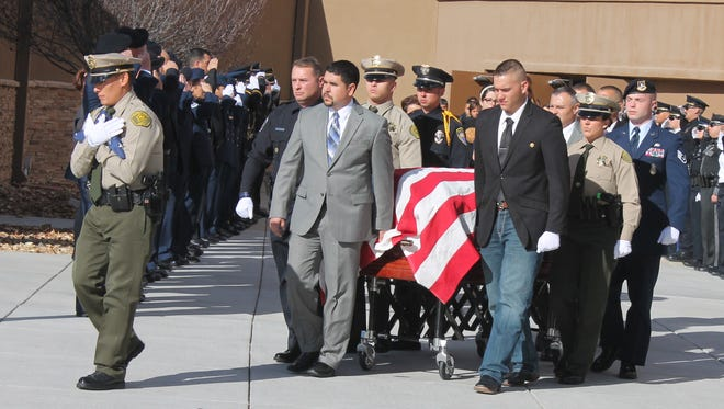 The body of Valencia County Sheriff's Deputy Ryan Thomas is escorted out of Legacy Church in Albuquerque after a memorial service in his honor Saturday morning.