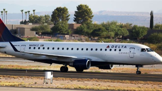 A Delta Compass Air passenger plane taxis as it is escorted along the Tucson International Airport tarmac on June 22, 2016, in Tucson, Ariz. Reports indicated an unruly passenger was taken into custody.