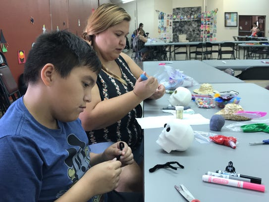 Sebastian Ybarra, 11, decorates alongside Yvonne Wright