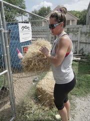 Lesa Whitley brings fresh straw for two dogs in backyard kennels built by C.H.A.I.N.E.D.