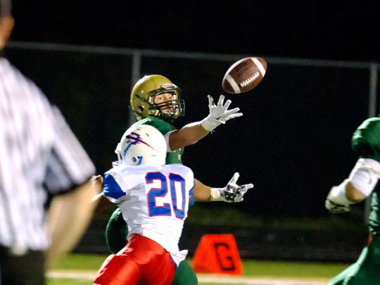Iowa City West's Oliver MArtin (8) reaches out for a pass as Davenport Central's Mario Patterson (20) defends during the second half of play in Iowa City on Friday, September 25, 2015. West won the matchup 42-14 to win their first game of the season.