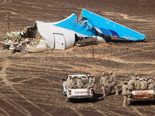 In this photo made available Monday, Nov. 2, 2015, and provided by Russian Emergency Situations Ministry, Egyptian Military on cars approach a plane's tail at the wreckage of a passenger jet bound for St. Petersburg in Russia that crashed in Hassana, Egypt, on Sunday, Nov. 1, 2015. The Russian cargo plane on Monday brought the first bodies of Russian victims killed in a plane crash in Egypt home to St. Petersburg, a city awash in grief for its missing residents.