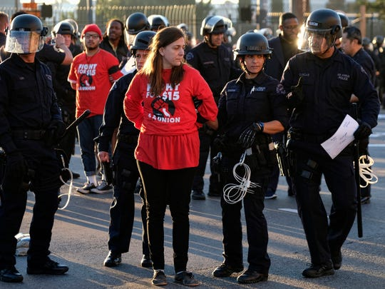 """Protesters are arrested and taken into custody during a wage protest in downtown Los Angeles on Tuesday, Nov. 29, 2016. A few dozen protesters blocked a downtown Los Angeles intersection as part of a national wave of demonstrations in support of higher wages and workers' rights. Police stood by as the peaceful demonstrators formed a circle in the street early Tuesday while hoisting signs saying """"the whole world is watching"""" and """"Fight for $15."""""""