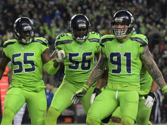 Seattle Seahawks defensive end Frank Clark (55), defensive end Cliff Avril (56) and defensive end Cassius Marsh (91) celebrate after a sack against the Los Angeles Rams during a NFL football game at CenturyLink Field.
