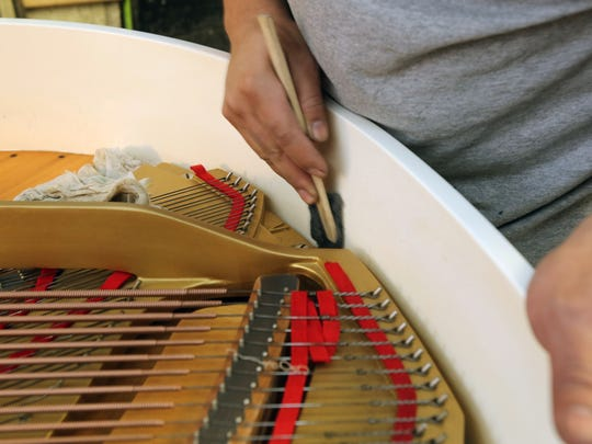 Cesar Ortega works on cleaning a Yamaha Baby Grand Piano at the Craftsman Piano workshop in the YoHo Arts complex on Nepperhan Avenue in Yonkers.