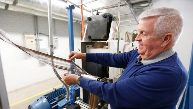 National Audio Company president and co-owner Steve Stepp shows a test strip of audiocassette tape that was not coated properly by the machine. The company is in the process of testing a new machine used to manufacture the tape used in audiocassettes.
