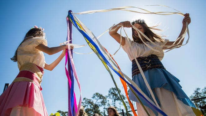 Izzy Janoyan, 14, left, and Mia Sciacqua,14, right, untangle ribbons after a maypole dance during the Medieval Faire at The Village School in Naples on Thursday, April 5, 2018.