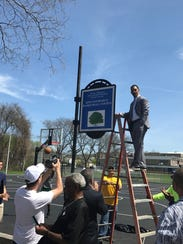 King Rice unveils a sign to show Columbus Park's basketball
