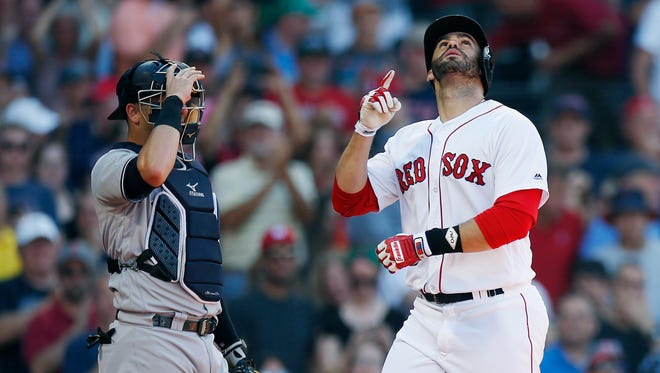 Boston Red Sox's J.D. Martinez, right, celebrates his solo home run in front of New York Yankees' Austin Romine during the fourth inning of a baseball game in Boston, Saturday, Aug. 4, 2018.