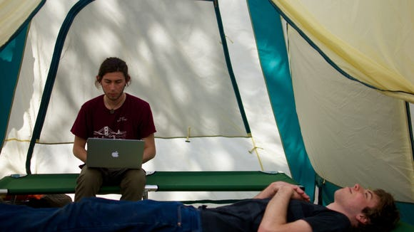 Two Labor Coalition members prepare to camp out in one of the tents they have set up. (Liam Brady / The Tufts Daily)