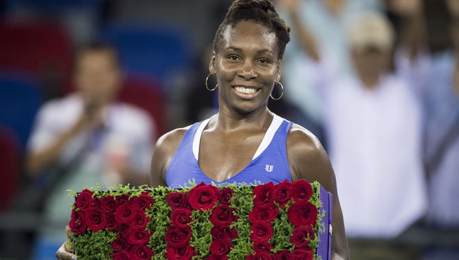 Venus Williams celebrates her 700th career win after beating Julia Goerges of Germany in their women's singles match during the Wuhan Open in China's Hubei province on Sept. 29, 2015.