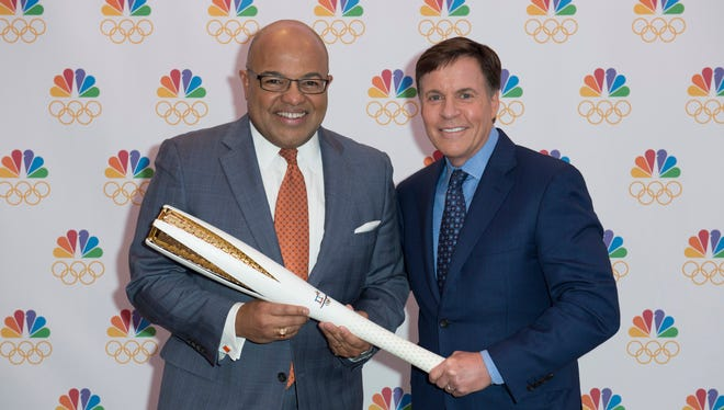 Bob Costas, right, passes a ceremonial Olympic torch to Mike Tirico after it was announced Tirico would replace Costas as primetime host of the Olympics on NBC.