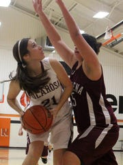 Gracie Hooten, left, is heavily defended by a Magdalena player. Tularosa defeated Magdalena 63-48.