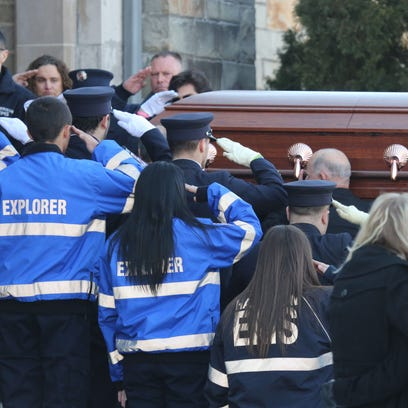 Explorers salute as caskets are carried into the church
