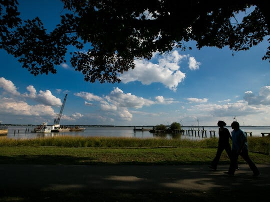 Pedestrians walk along the Delaware River in New Castle on Tuesday. A new pier is planned on the waterfront.