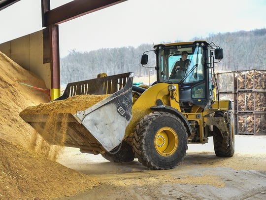Chester Dell moves sawdust with a backhoe at Gish Logging on Thursday, Dec. 1, 2016. The sawdust will be burned to make heat that will power the kiln.