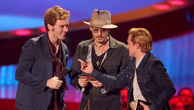 Sam Claflin, left, and Josh Hutcherson, right, accept the movie of the year award for 'The Hunger Games: Catching Fire' from actor Johnny Depp, center, onstage at the 2014 MTV Movie Awards on April 13 in Los Angeles.
