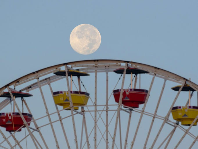 """The perigee full moon, also known as a """"supermoon,"""" is seen over the Ferris wheel at Santa Monica (Calif.) Pier on Aug. 11."""