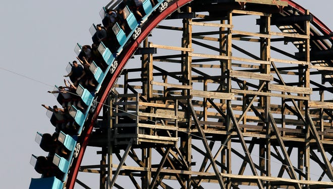 Visitors to Six Flags ride the Texas Giant as they crest the top of the tallest drop on the roller coaster ride in Arlington, Texas, Saturday Sept. 14, 2013. Six Flags has reopened the Texas Giant roller coaster for the first time since a rider fell 75 feet to her death.