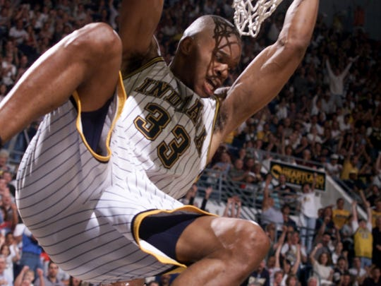 Antonio Davis hangs on the rim after a dunk in second half action against Milwaukee in 1999.