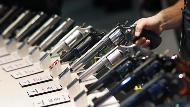 Handguns are displayed at the Smith & Wesson booth at the January Shooting, Hunting and Outdoor Trade Show in Las Vegas. Nearly two-thirds of Americans express support for stricter gun laws, according to an Associated Press-GfK poll released July 23. A majority of poll respondents oppose banning handguns.