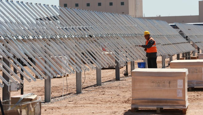 A worker in March assembled hardware to hold solar panels at El Paso Electric's community solar plant at Zaragoza and Montana in far East El Paso County.
