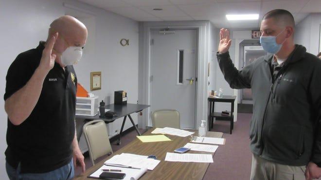 Ridgeley mayor Mark Jones (left)  swears in new police chief Cody Kroll as he prepares to serve residents and the town.Tribune photo by Ronda Wertman