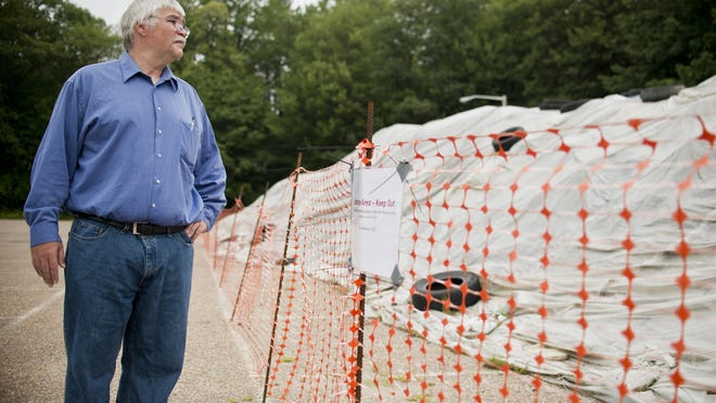 Jim Holway, member of the Wards 4/7 Neighborhood Planning Assembly, looks at a pile of dirt at Leddy Park containing low levels of arsenic, lead and other contaminants.